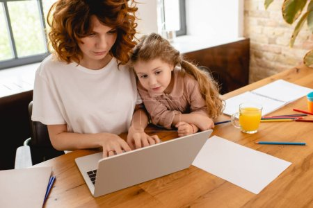 Photo for Cute kid looking at laptop while freelancer mother working from home - Royalty Free Image