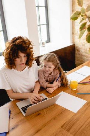 Photo pour Mignon enfant regardant ordinateur portable tandis que la mère pigiste travaillant de la maison - image libre de droit