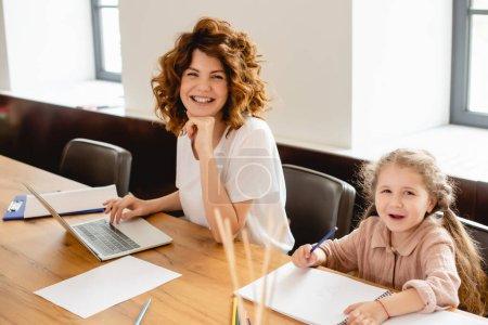 Photo pour Focus sélectif de mère freelancer heureuse et frisée souriant près du dessin d'enfant à la maison - image libre de droit