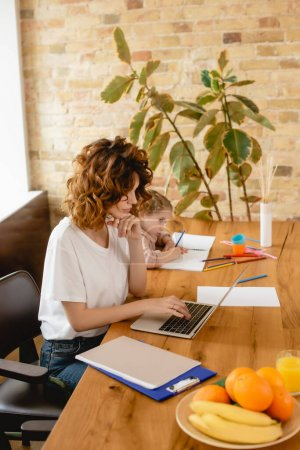 freelancer mother using laptop while cute daughter drawing at home