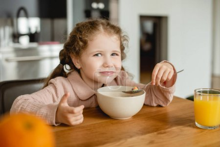 selective focus of kid holding spoon near bowl with corn flakes and glass of orange juice