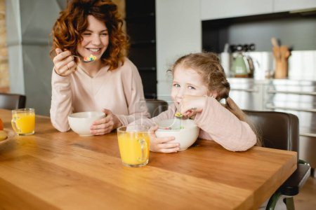 Photo for Cheerful mother and daughter holding spoons near bowls with corn flakes and glasses of orange juice - Royalty Free Image