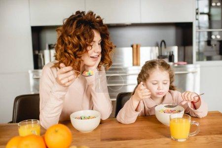 Photo pour Mère bouclée et adorable enfant tenant des cuillères près des bols avec des flocons de maïs et des verres de jus d'orange - image libre de droit
