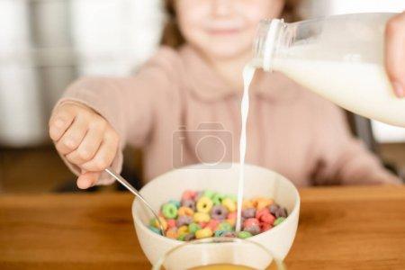 Photo pour Foyer sélectif de lait versant dans le bol avec de savoureux flocons de maïs près de mignon enfant - image libre de droit