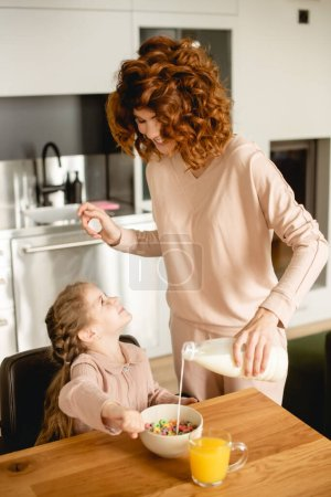 happy mother pouring milk into bowl with tasty corn flakes near cute kid