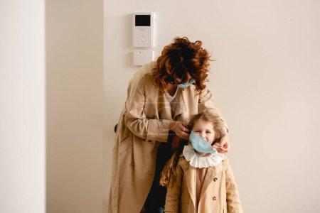 Photo pour Mère à tête rouge vêtue d'un manteau de tranchée portant un masque médical sur sa mignonne fille - image libre de droit