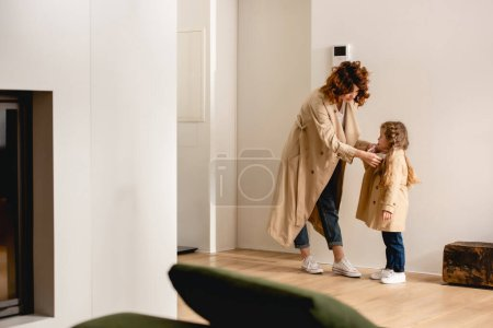 Photo for Selective focus of mother touching trench coat on daughter - Royalty Free Image