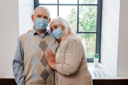 Photo pour Bouleversé couple âgé dans des masques médicaux étreignant à la maison pendant l'isolement personnel - image libre de droit