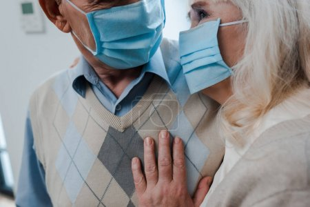 Photo pour Vue recadrée du couple âgé dans des masques médicaux étreignant à la maison pendant l'isolement personnel - image libre de droit