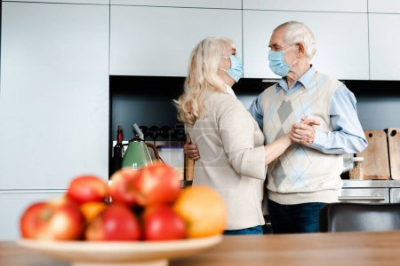 elderly couple in medical masks dancing on kitchen with apples during self isolation, selective focus