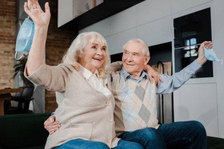 Photo pour Joyeux couple de personnes âgées tenant des masques médicaux sur le canapé après l'isolement - image libre de droit
