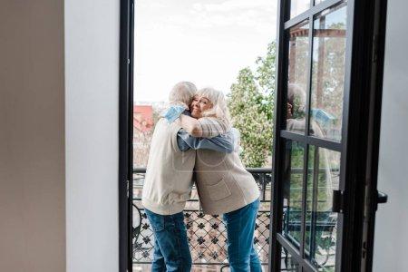 Photo pour Heureux couple âgé tenant masques médicaux et câlins sur le balcon après auto isolement - image libre de droit