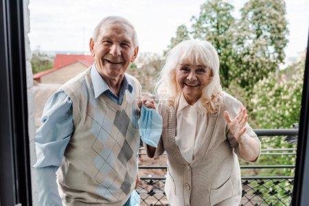 Photo pour Heureux couple âgé tenant des masques médicaux tout en se tenant sur le balcon après auto isolement - image libre de droit
