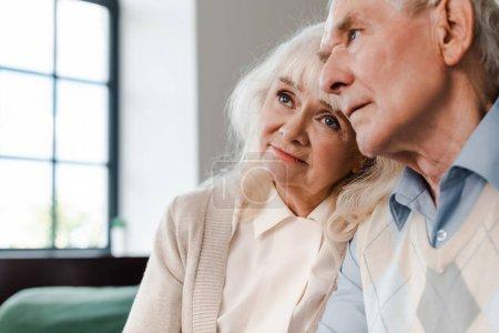 Photo for Sad elderly couple sitting together at home on quarantine - Royalty Free Image