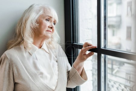 sad elderly woman looking through window during self isolation