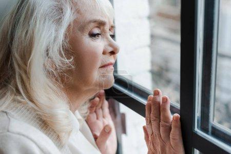 Photo pour Bouleversé femme âgée debout près de la fenêtre pendant la quarantaine - image libre de droit