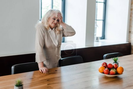 tired elderly woman with headache standing at table with fruits during quarantine