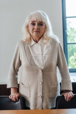 Photo pour Femme âgée solitaire debout à la table pendant l'isolement personnel - image libre de droit