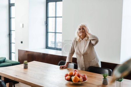 senior woman having headache and standing at table with fruits during self isolation