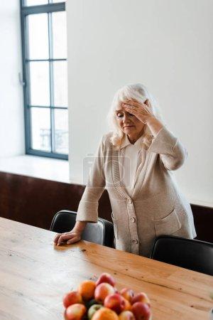 Foto de Mujer anciana cansada con dolor de cabeza de pie en la mesa con frutas durante el autoaislamiento - Imagen libre de derechos
