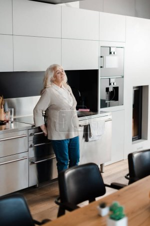 lonely sad elderly woman standing at kitchen during quarantine
