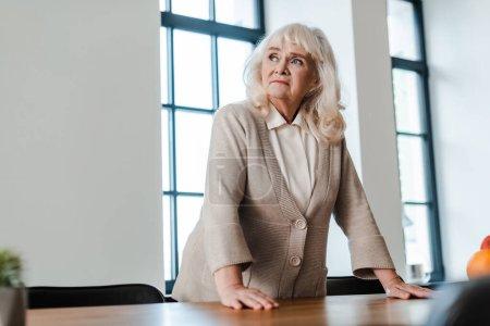 Photo pour Triste femme âgée debout à la table pendant l'isolement personnel - image libre de droit