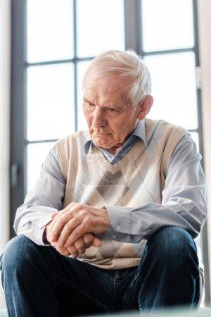 Photo pour Bouleversé homme âgé assis seul sur le canapé pendant l'isolement personnel - image libre de droit