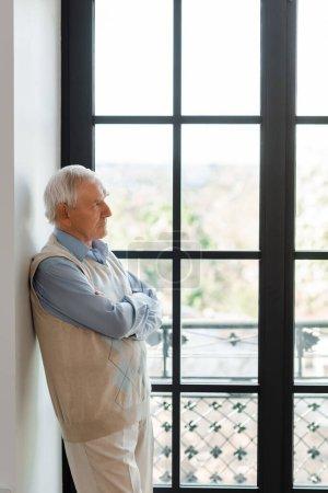 Photo pour Triste homme âgé avec les bras croisés debout près de la fenêtre pendant la quarantaine - image libre de droit