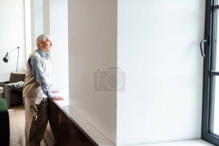 Photo for Sad elderly man standing near window during self isolation - Royalty Free Image