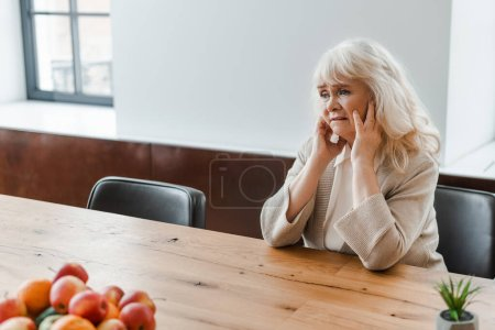 sad lonely senior woman sitting at table with fruits during quarantine