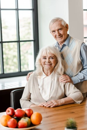 Photo for Smiling elderly couple sitting at table with fruits - Royalty Free Image