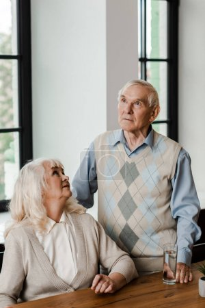 Photo for Upset elderly couple with glass of water at home on self isolation - Royalty Free Image