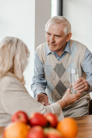 Photo for Worried senior husband and sick wife with pills and glass of water at home during quarantine - Royalty Free Image