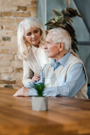Photo for Upset senior wife and husband hugging and sitting at home on quarantine - Royalty Free Image