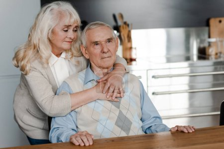 Photo for Sad elderly wife and husband hugging and sitting at home on quarantine - Royalty Free Image