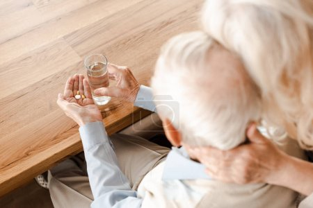 Photo for Upset sick elderly couple with pills and glass of water at home on self isolation, selective focus - Royalty Free Image