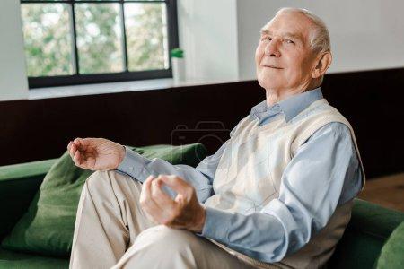 Photo pour Homme âgé heureux méditant sur le canapé à la maison pendant l'isolement personnel - image libre de droit