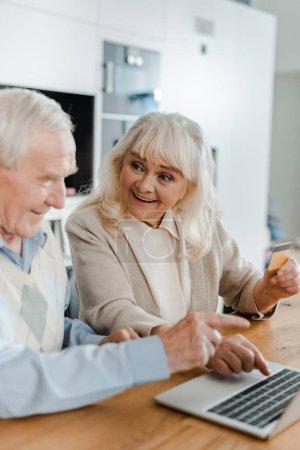 Photo pour Surpris couple de personnes âgées faisant des achats en ligne avec carte de crédit et ordinateur portable à la maison pendant la quarantaine - image libre de droit
