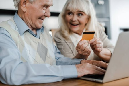 excited senior couple shopping online with credit card and laptop at home during self isolation