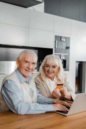 Emotionales Senioren-Paar kauft während der Selbstisolierung zu Hause online mit Kreditkarte und Laptop ein
