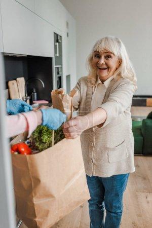 Photo for Happy elderly woman taking food delivery during coronavirus pandemic - Royalty Free Image