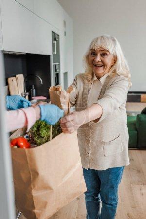 Photo pour Heureuse femme âgée prenant livraison de nourriture pendant la pandémie de coronavirus - image libre de droit