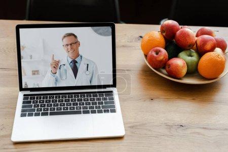 Photo pour Gros plan de l'ordinateur portable avec un médecin souriant à l'écran sur la table avec des fruits - image libre de droit