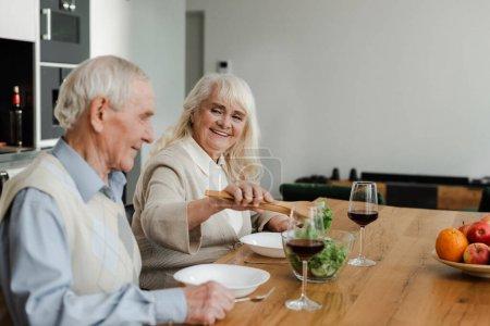 Photo pour Sourire couple âgé dîner avec du vin et de la salade à la maison sur l'isolement - image libre de droit
