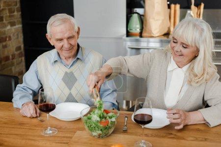 Photo pour Souriant couple de personnes âgées dîner avec du vin rouge et salade à la maison en quarantaine - image libre de droit