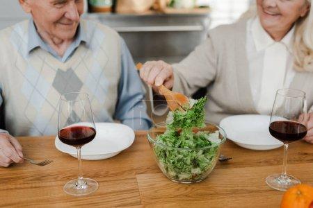 Photo pour Vue recadrée de heureux couple de personnes âgées dînant avec du vin et de la salade à la maison en quarantaine - image libre de droit