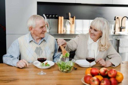 Photo pour Heureuse épouse aînée et mari dînant avec du vin et de la salade à la maison en quarantaine - image libre de droit