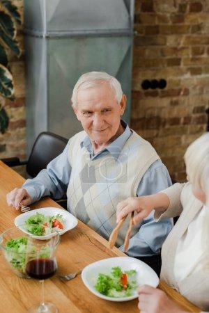 Photo pour Couple âgé positif dîner avec vin rouge et salade à la maison en quarantaine - image libre de droit