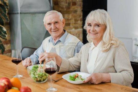 Photo pour Sourire couple aîné dîner avec du vin et salade à la maison sur l'isolement personnel - image libre de droit