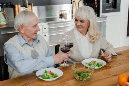 Photo pour Heureux mari et femme aînés dîner avec du vin et de la salade à la maison sur l'isolement personnel - image libre de droit